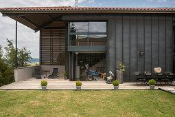 Rasen und Terrasse um ein modernes Haus mit dunkler Fassade