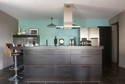 Modern, open-plan kitchen with black cabinets and pale blue wall