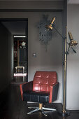 Retro-style leather armchair next to gilt standard lamp in hallway