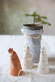 Perforated pottery bells in front of tiny potted fir tree