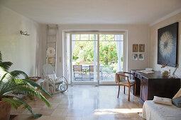 Schlichtes Wohnzimmer mit Schaukelstuhl und Schreibtisch