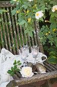 Weingläser als Windlichter auf einem verwitterten Gartenstuhl