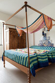 Striped blanket on four-poster bed with tiles on wall at head end