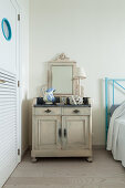Vintage accessories on old, shabby-chic cabinet used as bedside table