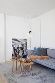 Graues Polstersofa mit Kissen und Tierfell, dreier Couchtisch-Set auf grauem Teppich im Wohznimmer