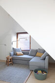 Cushions on grey corner sofa in attic room