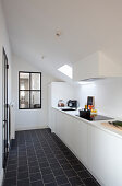 White fitted kitchen with black floor tiles