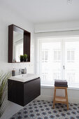 Sink and mirror on white tiled wall, wooden stool in front of window with louvre blinds in bathroom