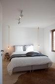 Doppelbett, Hocker als Nachttisch und Pendelleuchten im Schlafzimmer