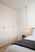 Fitted wardrobes, double bed, stool used as bedside table and pendant lamp in bedroom