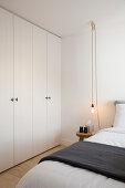 Kleiderschrank, Doppelbett, Hocker als Nachttisch und Pendelleuchte im Schlafzimmer