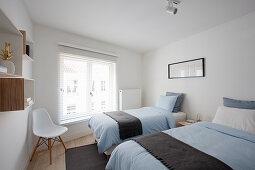 Zwei Einzelbetten und Klassikerstuhl im Gästezimmer