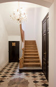 Foyer with tiled floor, wooden staircase and chandelier