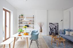 Esstisch mit Schalenstühlen und Sitzbank vor Balkontür und graues Polstersofa mit Couchtisch-Set in offenem Wohnraum