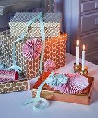 Verpackte Geschenke mit Metallic-Papier und Rosetten als Deko