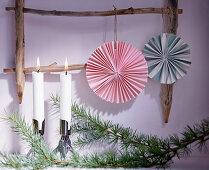 Papierrosetten hängen an einer Holzleiter vor Kerzen und Nadelzweig