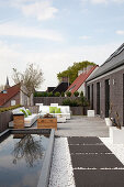 Rectangular pond and seating area on large modern roof terrace