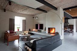 Polstermöbel aus Leder im offenen Wohnzimmer mit Kaminfeuer