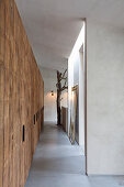 Rough wooden fitted cupboards in corridor with concrete floor
