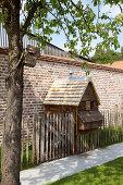 Wooden chicken coop against brick garden wall