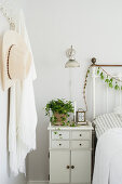 Potted ivy on bedside table in white bedroom