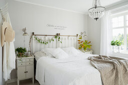 Wall tattoo above bed in vintage bedroom painted white
