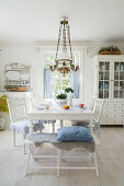 Bench and chairs around white table in vintage-style dining room
