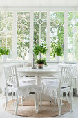 Cushions with ruffles on white chairs at round table in Scandinavian conservatory