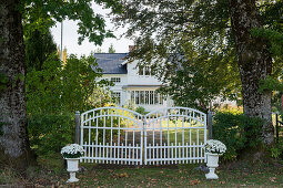 Gates of driveway leading to white Swedish house in woodland