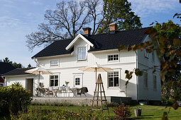White Swedish house with black roof and terrace