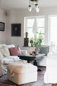 White upholstered furniture around black coffee table