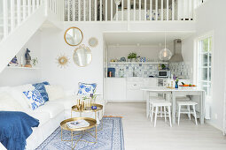 White couch, white dining table and kitchen below gallery in open-plan interior