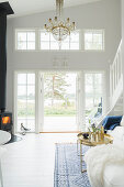 Chandelier and log-burner in high-ceilinged, white living room with terrace doors