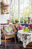 Colourful cushions on seats and round table in conservatory