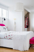 Double bed in white bedroom with pink accents and walk-in wardrobe behind curtain