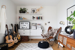 Guitar, white wall-mounted shelves, Butterfly chair and large phono sideboard in music room