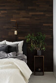 Houseplant on bedside table in front of wood-clad wall