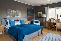 Blue blanket on bed in bedroom with grey walls