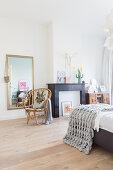Black mantelpiece in bedroom with wooden floor