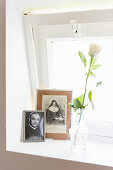 White rose and photos of priest and nun on windowsill