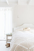 Lacy blanket on bed in bright bedroom decorated entirely in white