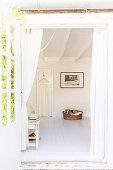 View through open terrace doors into bedroom with dog in basket on floor