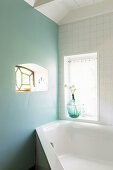 Small window in pale turquoise wall in bathroom with corner bathtub