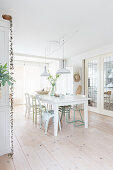 Various chairs around white table in bright dining room