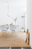 White dining area: dining table and classic chairs on wooden floorboards