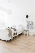 Double bed and ladder used as valet stand in white bedroom with wooden floor