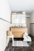 Washstand with wooden fronts below mirror wall cabinet in bathroom with black marble floor tiles