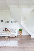 Sofa below staircase in simple living room decorated entirely in white