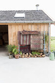 Ethnic rug hung from frame outside barn