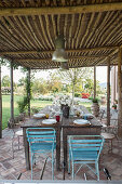 Two narrow wooden tables pushed together and used as dining table on Mediterranean terrace